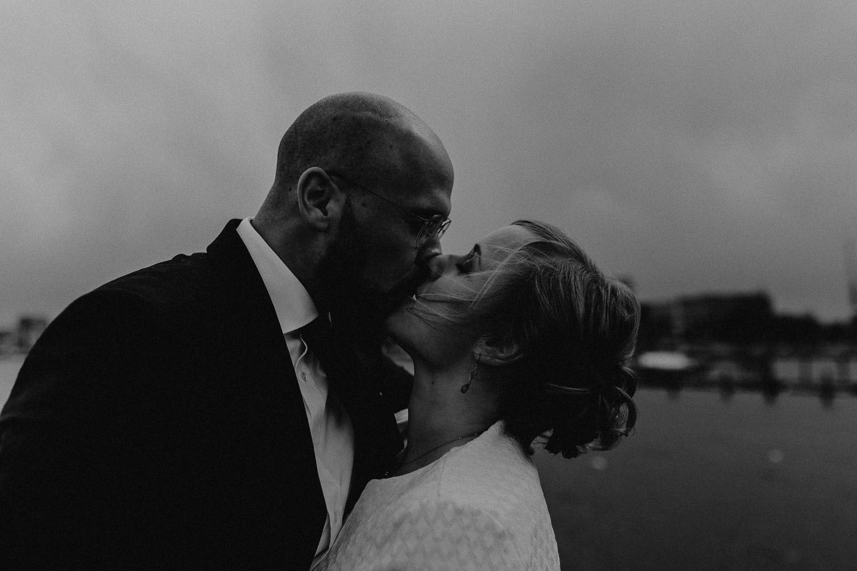 Aufgenommen von Hochzeitsfotograf Kupfergold Photographie aus Rostock. Zu sehen ist ein Foto eines Elopments im Rostocker Stadthafen.  Brautpaarshooting mit Skyline von Rostock im Hintergrund